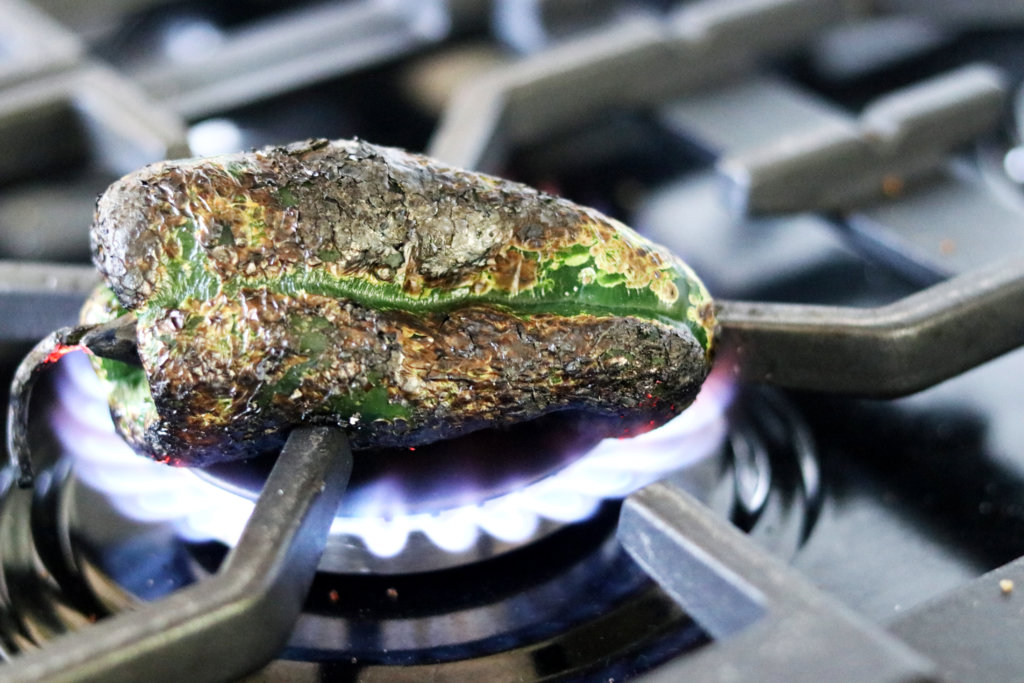 A poblano pepper being fire-roasted
