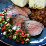 A plate of Santa Maria style barbecue, with tri-tip, beans, salsa, and garlic bread