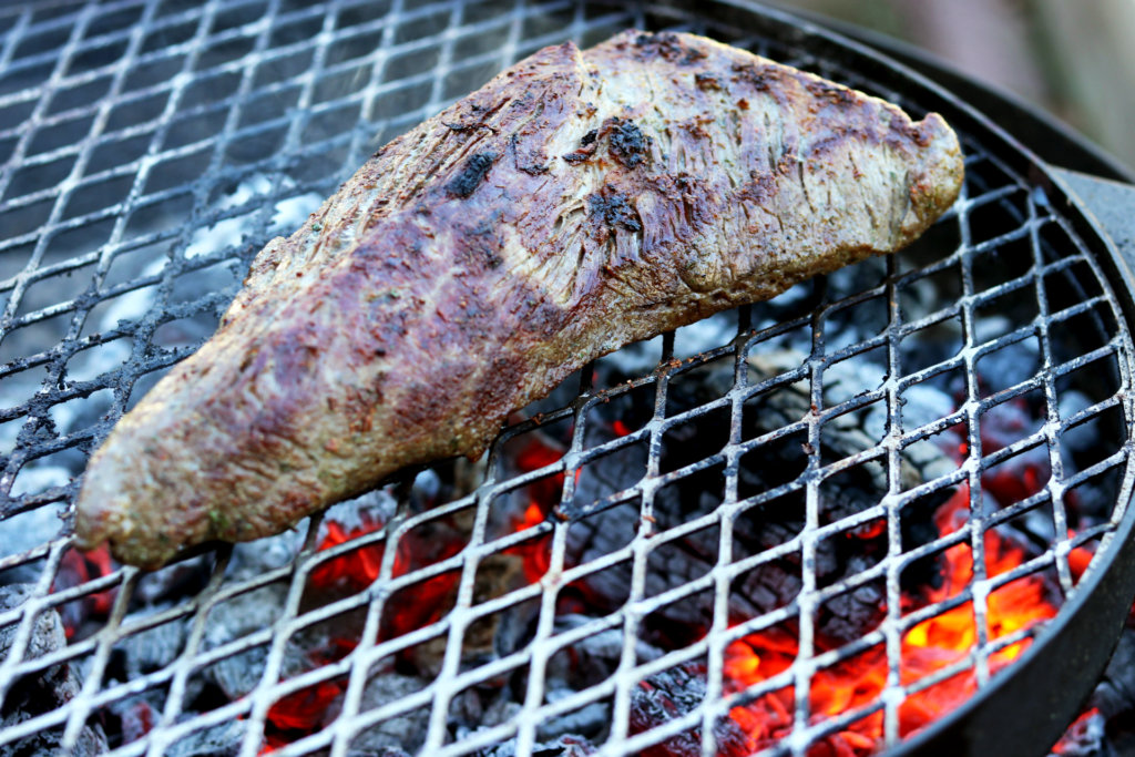 tri-tip on a grill with glowing coals